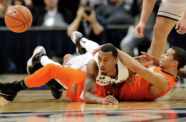 Connecticut's Ryan Boatright, top, tangles with Syracuse's Michael Carter-Williams, bottom, during the second half of an NCAA college basketball game in Hartford, Conn., Wednesday, Feb. 13, 2013. Connecticut won 66-58. (AP Photo/Jessica Hill) Photo: Jessica Hill, Associated Press / FR125654 AP