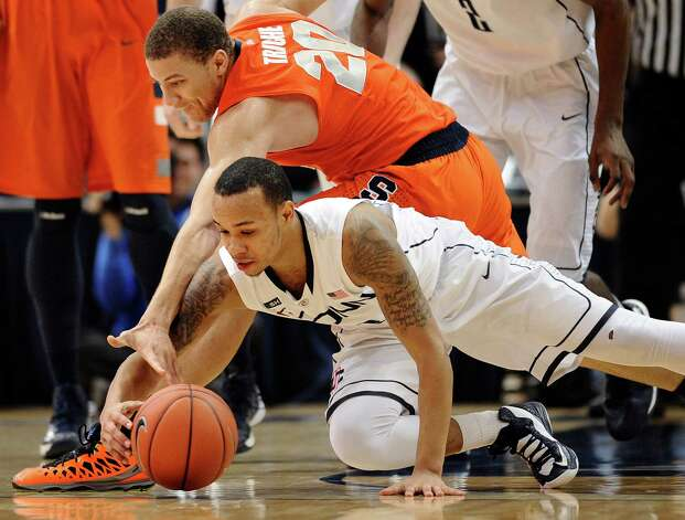 Connecticut's Shabazz Napier, bottom, and Syracuse's Brandon Triche, top, chase a loose ball during the second half of an NCAA college basketball game in Hartford, Conn., Wednesday, Feb. 13, 2013. Connecticut won 66-58. (AP Photo/Jessica Hill) Photo: Jessica Hill, Associated Press / FR125654 AP