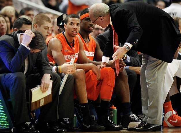 Syracuse head coach Jim Boeheim, right, speaks with Syracuse's Michael Carter-Williams after Carter-Williams received his fourth foul during the second half of an NCAA college basketball game against Connecticut in Hartford, Conn., Wednesday, Feb. 13, 2013. Connecticut won 66-58. (AP Photo/Jessica Hill) Photo: Jessica Hill, Associated Press / FR125654 AP