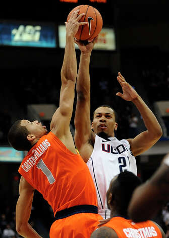 Syracuse's Michael Carter-Williams, left, blocks a shot-attempt by Connecticut's Omar Calhoun, right, during the second half of an NCAA college basketball game in Hartford, Conn., Wednesday, Feb. 13, 2013. Connecticut won 66-58. (AP Photo/Jessica Hill) Photo: Jessica Hill, Associated Press / FR125654 AP