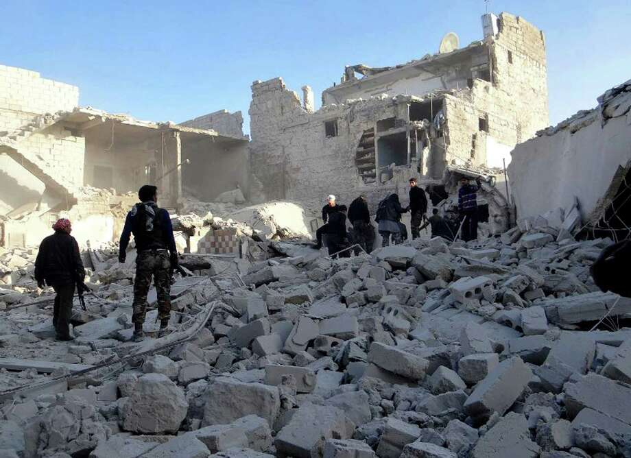 Citizen journalism image provided by Aleppo Media Center AMC which has been authenticated based on its contents and other AP reporting, shows Syrian rebels stand in the rubble of damaged buildings due to government airstrikes, in the neighborhood of Karam Tarab near Aleppo International Airport, in Aleppo, Syria, Wednesday, Feb. 13, 2013. Syrian rebels fought pitched battles Wednesday against regime forces at a military base that protects a major airport in the country's north in fighting that has left more than 40 government troops dead, opposition activists said. (AP Photo/Aleppo Media Center AMC) Photo: Anonymous