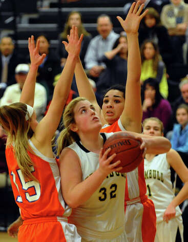 Danbury's #15 Rebecca Gartner, left, and teammate #25 Kayla Handberry, in back, put pressure on Trumbull's #32 Erin Moore as she attempts a shot, during girls basketball action in Trumbull, Conn. on Wednesday February 13, 2013. Photo: Christian Abraham / Connecticut Post