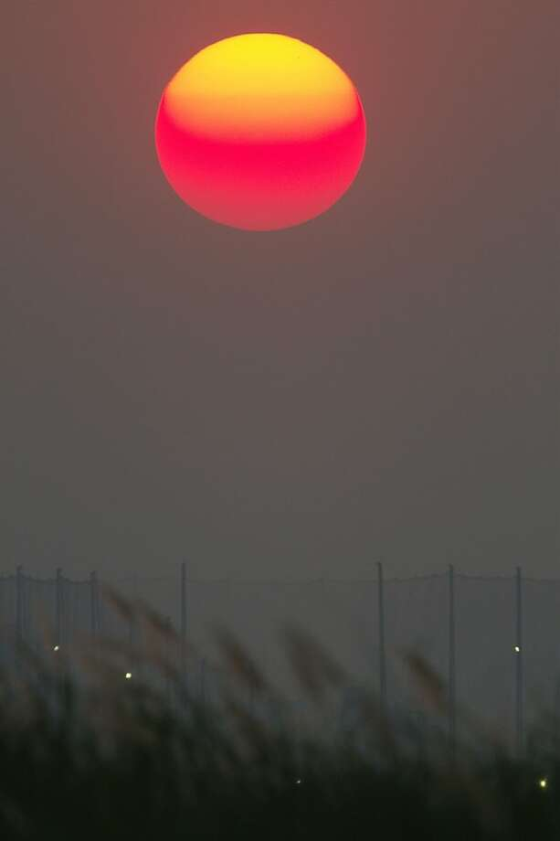 In this Tuesday, Feb. 12, 2013 photo, the sun goes down over the Mekong river in the outskirt of Phnom Penh, Cambodia. (AP Photo/Heng Sinith) Photo: Heng Sinith, Associated Press