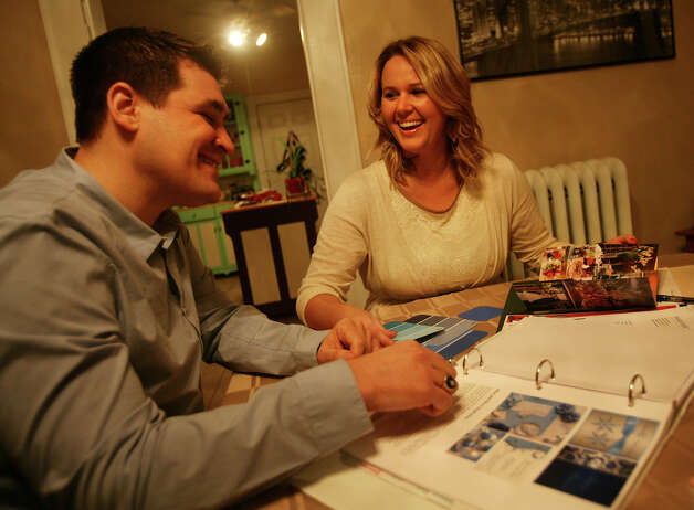 Tony Kellogg, 28, and Katie Hanscom, 27, pour over some of their wedding planning materials in their Fairfield apartment on Monday, February 11, 2013. The couple are getting married after dating for four-and-a-half years. Photo: Brian A. Pounds / Connecticut Post