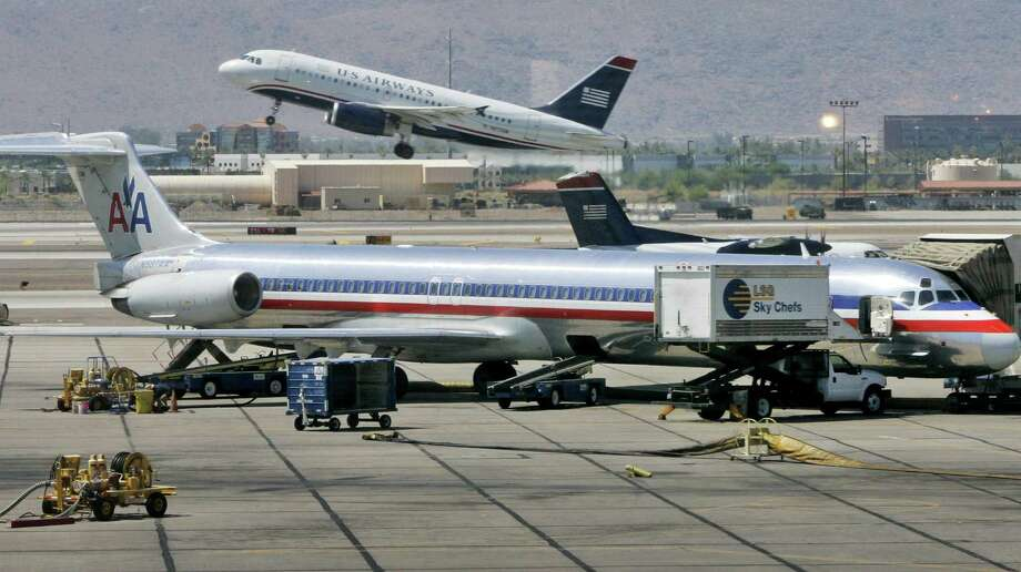 FILE - In this June 23, 2008 file photo, a US Airways jet takes off as an American Airlines jet is prepped for takeoff at Sky Harbor International Airport in Phoenix. The merger of US Airways and American Airlines has given birth to a mega airline with more passengers than any other in the world. (AP Photo/Matt York, File) Photo: Matt York