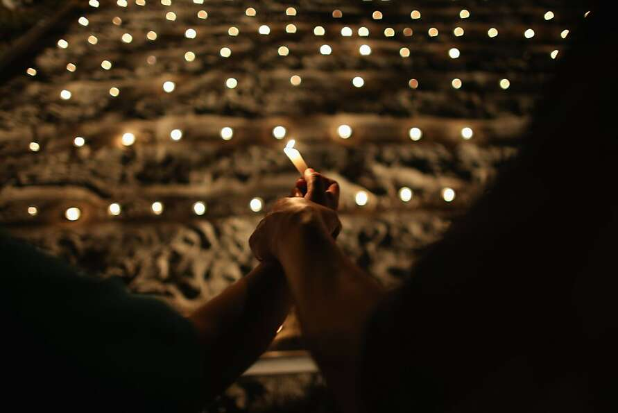 FLORIDA CITY, FL - FEBRUARY 13: People hold a candle during a vigil at the Branches United Methodist