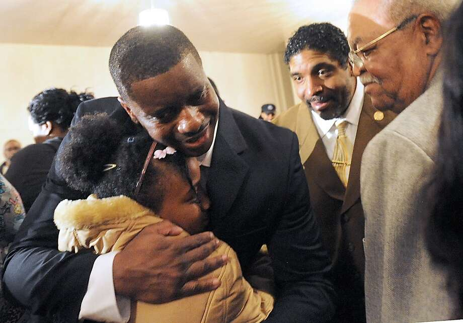 John McNeil hugs an unidentified youngster after holding a press conference in his hometown of Wilson, N.C.,  just a day after being released from a Georgia prison. McNeil served 6 years after being convicted of killing a man in his yard, who supporters say was threatening him and his family. Tuesday McNeil was allowed to plead to a lesser offense and was released. (AP Photo/The Wilson Times, Brad Coville) Photo: Brad Coville, Associated Press