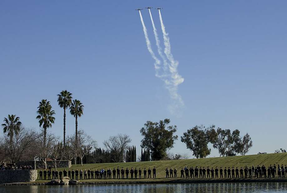 Police officers stand in attention as planes flyover in formation during a committal for Riverside Police officer Michael Crain, who was allegedly shot to death by accused killer and fired Los Angeles police officer, Christopher Dorner, at the Riverside National Cemetery in Riverside, Calif., Wednesday, Feb. 13, 2013. (AP Photo/Damian Dovarganes) Photo: Damian Dovarganes, Associated Press