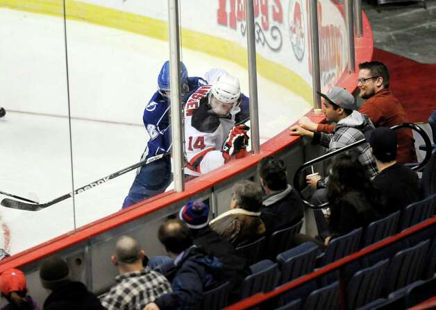 Fans watch as Albany Devils' Cam Janssen (14) is checked into the glass by Syracuse Crunch's Jean-Francois Jacques (22) during the first period of their AHL hockey game, Wednesday, Feb. 13, 2013, in Albany, N.Y. (Hans Pennink / Special to the Times Union) Pro Sports Photo: Hans Pennink / Hans Pennink