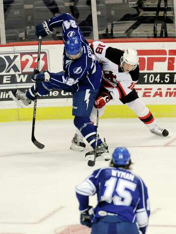 Syracuse Crunch's J.T. Wyman (15) watches teammate Jean -Phillippe Cote (24) battle Albany Devils' Harri Pesonen (18) for the puck during the second period of their AHL hockey game, Wednesday, Feb. 13, 2013, in Albany, N.Y. (Hans Pennink / Special to the Times Union) Pro Sports Photo: Hans Pennink / Hans Pennink