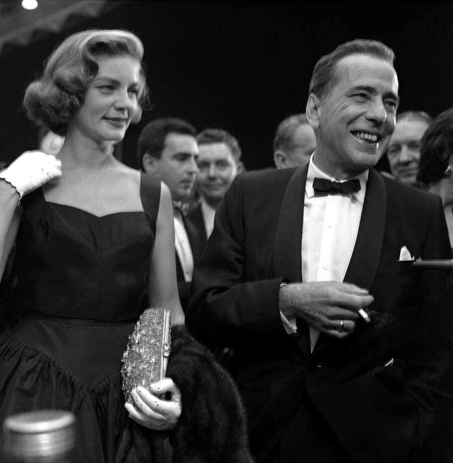 "Humphrey Bogart met Lauren Bacall when he was 44 and she was 19. Weeks after their first meeting, he ran into her on the Warner Brothers lot. ""I just saw your test,"" he said of the audition for ""To Have and Have Not."" ""We'll have a lot of fun together."" Did they ever. When you watch that film, ""everyone could see their love right there on the celluloid,"" their son, Steve, told People magazine in 1996. When they filmed the romantic scenes, Bacall was nervous. ""I realized that one way to hold my trembling head still was to keep it down, chin low, almost to my chest, and eyes up at Bogart,"" she wrote in her autobiography. That look became her trademark. The magazine reported that whenever they would talk on the phone for the next two years, his first words would be, ""Hello, Baby,"" and Becall wrote that her ""heart would literally pound."" They married on a friends Ohio farm in 1945 and remained by each other's side until his death from esophageal cancer in 1957. Photo: Getty Images"
