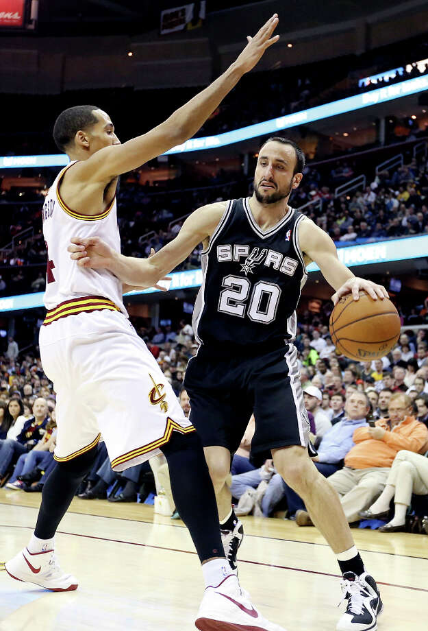 The Spurs' Manu Ginobili looks for room around Cleveland's Shaun Livingston during first half action Wednesday, Feb. 13, 2013, at the Quicken Loans Arena in Cleveland, Ohio. Photo: Edward A. Ornelas, San Antonio Express-News / © 2013 San Antonio Express-News