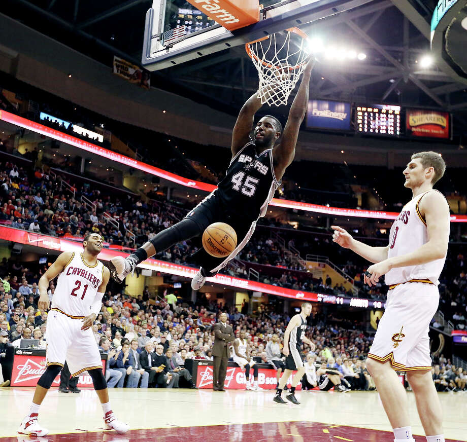 The Spurs' DeJuan Blair hangs on the rim after a dunk between Cleveland's Wayne Ellington and Tyler Zeller during first half action Wednesday, Feb. 13, 2013, at the Quicken Loans Arena in Cleveland, Ohio. Photo: Edward A. Ornelas, San Antonio Express-News / © 2013 San Antonio Express-News