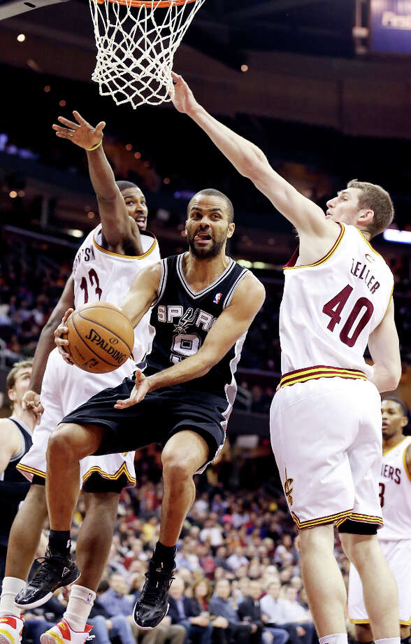 The Spurs' Tony Parker passes between Cleveland's Tristan Thompson (left) and Tyler Zeller during second half action Wednesday, Feb. 13, 2013, at the Quicken Loans Arena in Cleveland, Ohio. The Spurs won 96-95. Photo: Edward A. Ornelas, San Antonio Express-News / © 2013 San Antonio Express-News