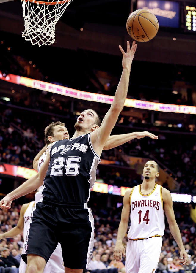 The Spurs' Nando De Colo shoots around Cleveland's Luke Walton during second half action Wednesday, Feb. 13, 2013, at the Quicken Loans Arena in Cleveland, Ohio. Cleveland's Shaun Livingston looks on. Photo: Edward A. Ornelas, San Antonio Express-News / © 2013 San Antonio Express-News