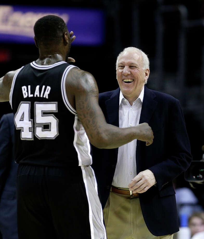 San Antonio Spurs coach Gregg Popovich high-fives DeJuan Blair during the first quarter of an NBA basketball game Wednesday, Feb. 13, 2013, in Cleveland. San Antonio won 96-95. Photo: Tony Dejak, Associated Press / AP