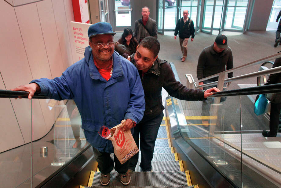 Holding a single rose be had just purchased for Valentine's Day, Donald Trammell and his girlfriend Bonita Abrams ride the escalator into City Target on Wednesday Feb. 13, 2013 in San Francisco Calif. Trammell, 51, and Abrams, 48, who met at The Arc San Francisco a non-profit that helps provide support for more than 600 clients with developmental disabilities, have been a couple for 15 years. Photo: Mike Kepka, The Chronicle / ONLINE_YES