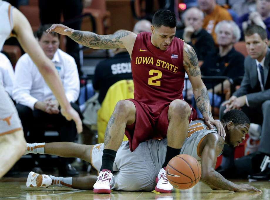 Iowa State's Chris Babb (2) falls on Texas' Julien Lewis (14) as they chase a loose ball during the second half of an NCAA college basketball game, Wednesday, Feb. 13, 2013, in Austin, Texas. Texas won 89-86 in double overtime.  (AP Photo/Eric Gay) Photo: Eric Gay, Associated Press / AP