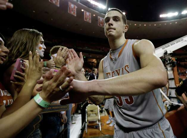Texas' Ioannis Papapetrou, right, celebrates with fans after the team's double overtime win over Iowa State in  an NCAA college basketball game, Wednesday, Feb. 13, 2013, in Austin, Texas. Texas won 89-86.  (AP Photo/Eric Gay) Photo: Eric Gay, Associated Press / AP