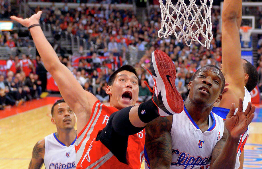 Rockets guard Jeremy Lin falls after putting up a shot as Clippers guard Eric Bledsoe defends and forward Matt Barnes watches. Photo: Mark J. Terrill, Associated Press / AP