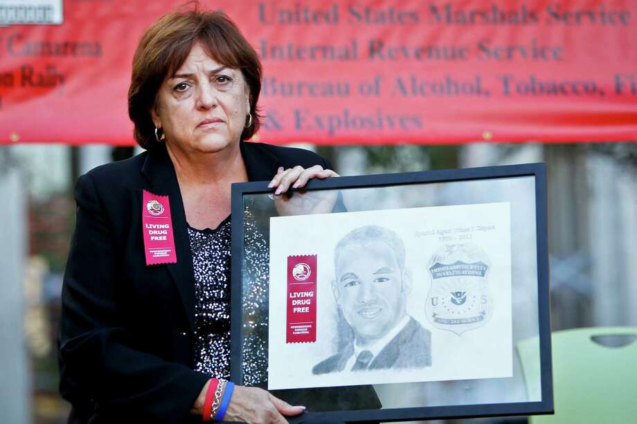 "Mary Zapata, the mother of, slain immigration agent Jaime Zapata, holds a plaque depicting her son during the Enrique ""Kiki"" Camarena Red Ribbon Rally at Tranquility park, Friday, Oct. 21, 2011, in Houston.  ( Michael Paulsen / Houston Chronicle ) Photo: Houston Chronicle"