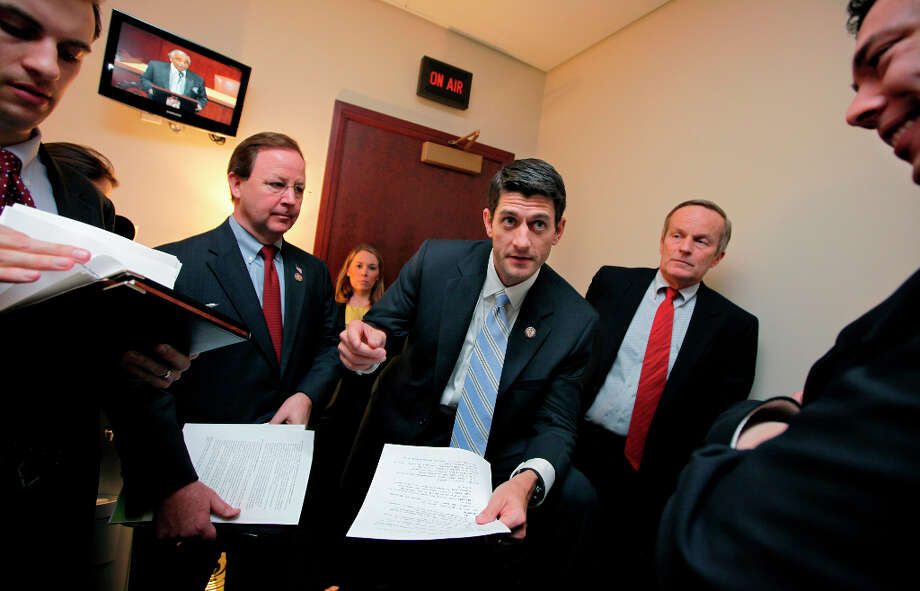 House Budget Committee Chairman Paul Ryan, R-Wis., works with Republican members of the committee on Capitol Hill in Washington, Tuesday, April 5, 2011. He is flanked by Rep. Tom McClintock, R-Calif., right, with Rep. Bill Flores, R-Texas, at left. The pace of budget negotiations in Congress is quickening as a deadline for a government shutdown looms at week's end. Photo: J. Scott Applewhite, AP / AP