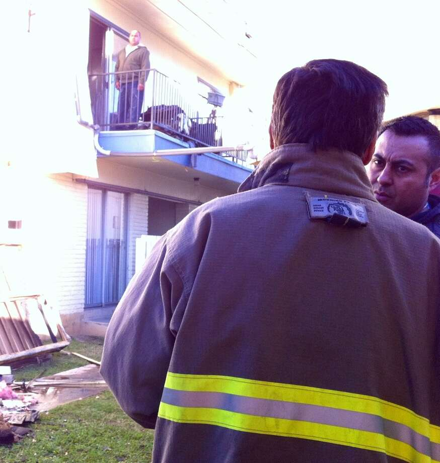 Battalion Chief Ron Rodriguez and paramedic Randy Zamora survey the damage caused by a fire at a unit in the Alamo Apartments on the 10300 block of Sahara Street early Thursday, Feb. 14, 2013. Photo: Ana Ley/Express-News