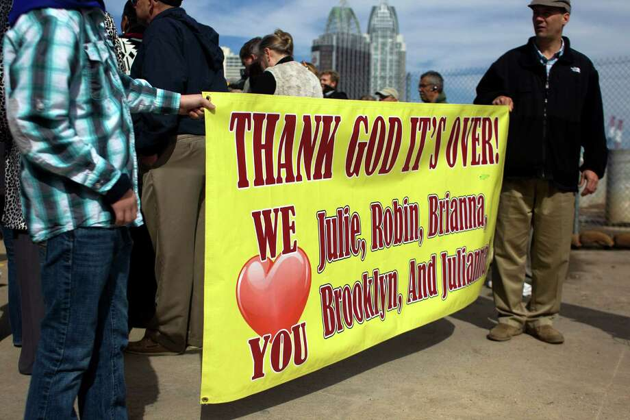 Family members hold a sign for their loved ones as people began gathering for the return of the Carnival Triumph ship at the Alabama Cruise Terminal Thursday, Feb. 14, 2013, in Mobile. 