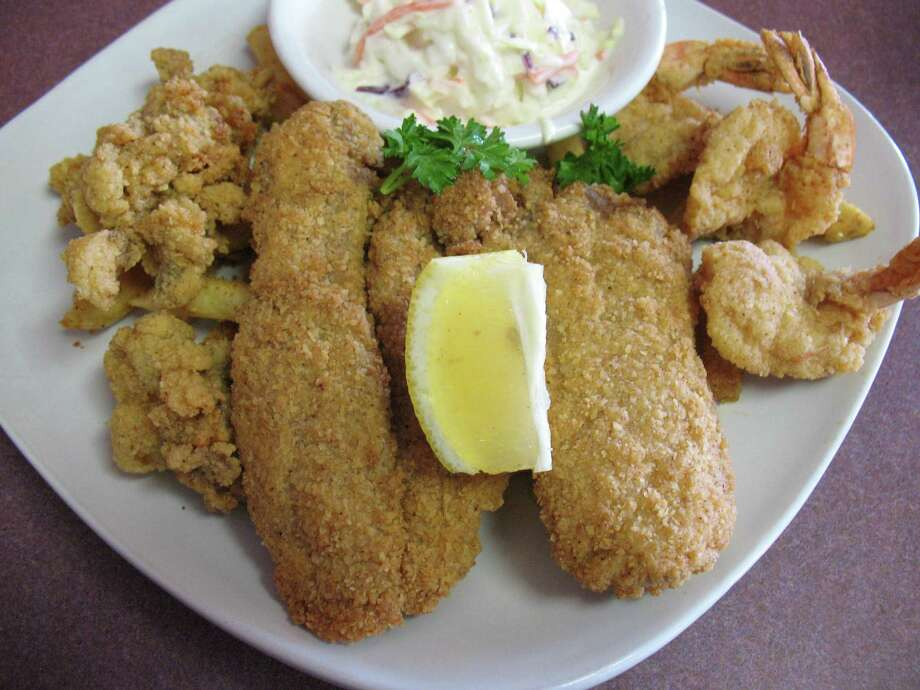 Sea & Wings on Blanco Road offers a Deluxe Fish Platter with two pieces of breaded catfish, three fried shrimp and four fried oysters, served with french fries and coleslaw. Photo: Jennifer McInnis / San Antonio Express-News