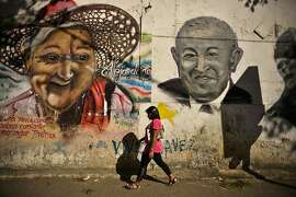 A woman walks past a mural of a bald, post-chemotherapy President Hugo Chavez in the Petare neighborhood on the outskirts of Caracas, Venezuela, on Tuesday, Jan. 8, 2013. Chavez, who is recovering from cancer surgery in Havana, ordered his government to weaken the exchange rate by 32 percent to 6.3 bolivars per dollar starting Feb. 13, Finance Minister Jorge Giordani told reporters Feb. 8. Photographer: Meridith Kohut/Bloomberg