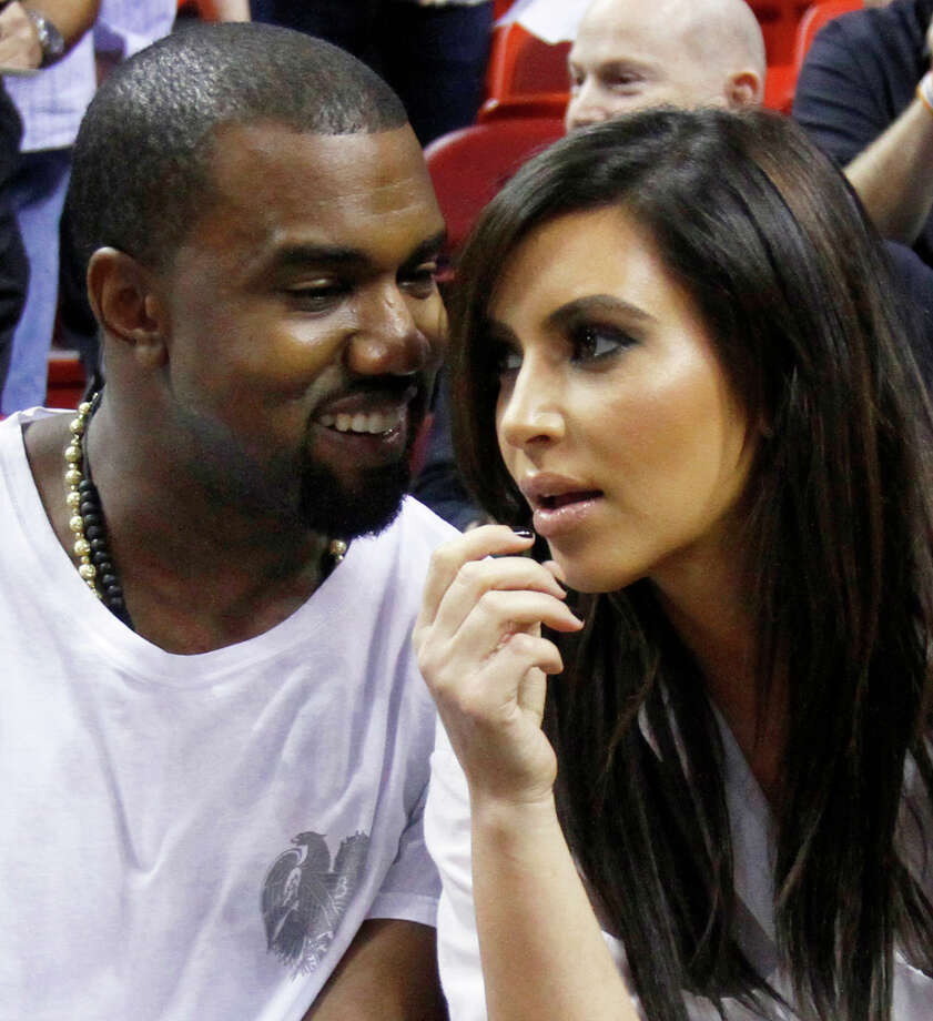 FILE - In this Dec. 6, 2012 file photo singer Kanye West, left, talks to his girlfriend Kim Kardashian before an NBA basketball game between the Miami Heat and the New York Knicks in Miami. Authorities say an airline employee is being investigated for allowing West and Kardashian to bypass a security checkpoint at New York's Kennedy Airport. (AP Photo/Alan Diaz, File) Photo: Alan Diaz