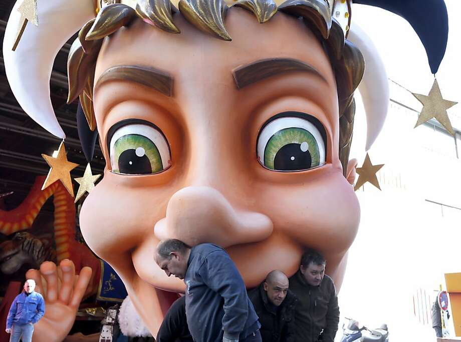 "King-sized appetite: The ""King of the Five Continents"" puts the bite on group of workers assembling the giant figure for the Nice carnival parade on the French Riviera. Photo: Valery Hache, AFP/Getty Images"