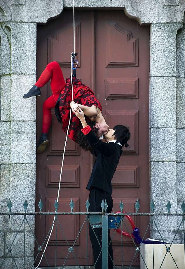Just like in Spider-Man: Yuga Hatta loves his fiancee, performer Pauliana Almeida, even though he sometimes finds her rappelling. She descended Clerigos' Tower during a performance to mark St. Valentine's Day in Porto, Portugal. Photo: Paulo Duarte, Associated Press
