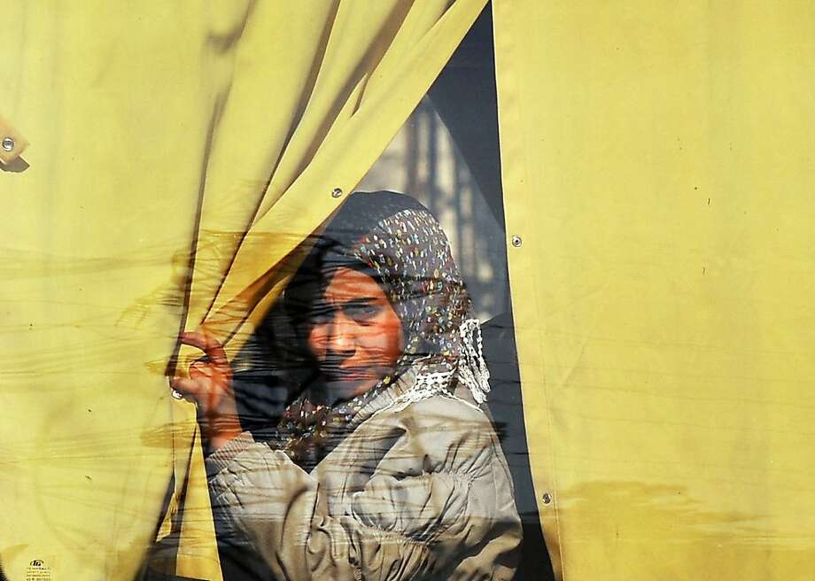 Bus-stop portrait: A Syrian woman is photographed through a bus window in the northern city of Aleppo. Photo: Bulent Kilic, AFP/Getty Images