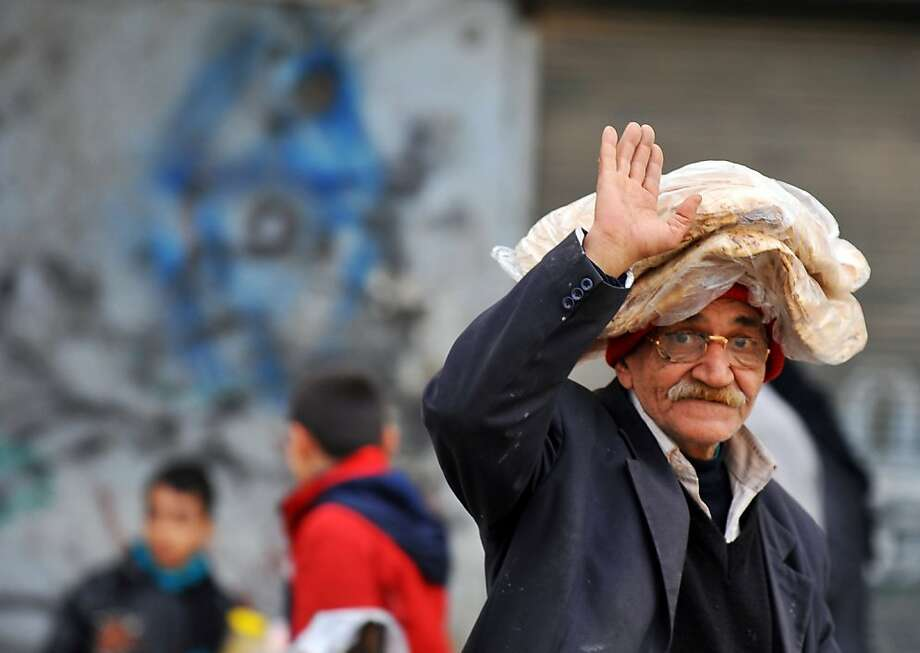 Do you think this old man wearing bread on his head is suggesting that the photographer get lost or greeting him with a friendly wave? Photo: Bulent Kilic, AFP/Getty Images