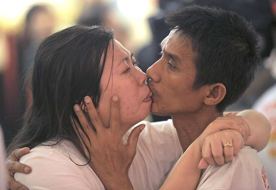 "Knotted Thais:Ekkachai Tiranara and his wife, Laksana, compete in a ""World's Longest Continuous Kiss"" contest on Valentine's Day at Thailand's Pattaya resort. Their lengthy lip lock of 58 hours, 35 minutes and 58 seconds set a new record, pending Guinness verification. Photo: Pornchai Kittiwongsakul, AFP/Getty Images"