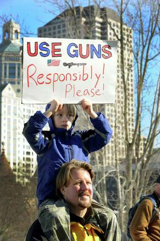 "Sebastian Killin, 7, of Newtown, sits on his father Tripp Killin's shoulders holding a sign promoting responsible gun use. A ""March for Change"" rally is held on the steps of the Capital in Hartford, Conn., Thursday, Feb. 14, 2013, to promote common sense and practical changes to the state's gun laws. Photo: Carol Kaliff / The News-Times"