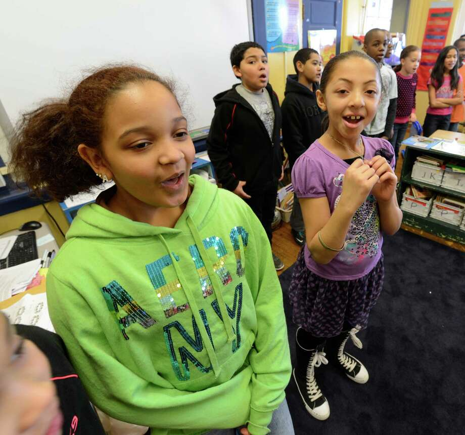 Aalycia Malacek 10, left, and Tyana Jackson, 10, right, are joined by other members of the Bel Canto Choir which is made up of students from Yates Elementary School sing a Valentines song for students in teacher Carrie White's split 1st and 2nd grade class on Valentine's Day Feb. 14, 2013 in Schenectady, N.Y.  The songfest was a fundraiser which benefits students who has a disability or need.    (Skip Dickstein/Times Union) Photo: SKIP DICKSTEIN / 00021122A