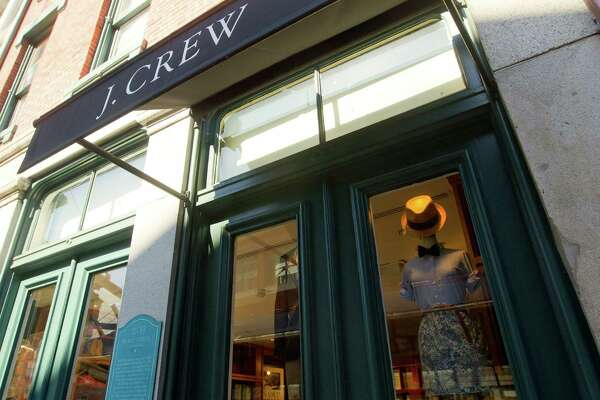 J. Crew Group Inc. signage hangs above a window display outside of a retail store in New York, U.S., on Tuesday, March 1, 2011. J. Crew Group shareholders voted in favor of TPG Capital and Leonard Green & Partners LP's takeover, capping Chief Executive Officer Millard Drexler's months-long effort to take the apparel chain private. Photographer: Jin Lee/Bloomberg