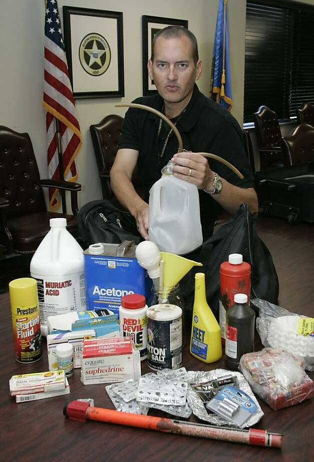 "Mark Woodward, spokesman for the Oklahoma Bureau of Narcotics, shows items used in the ""shake and bake"" method of manufacturing methamphetamine. Photo: AP"