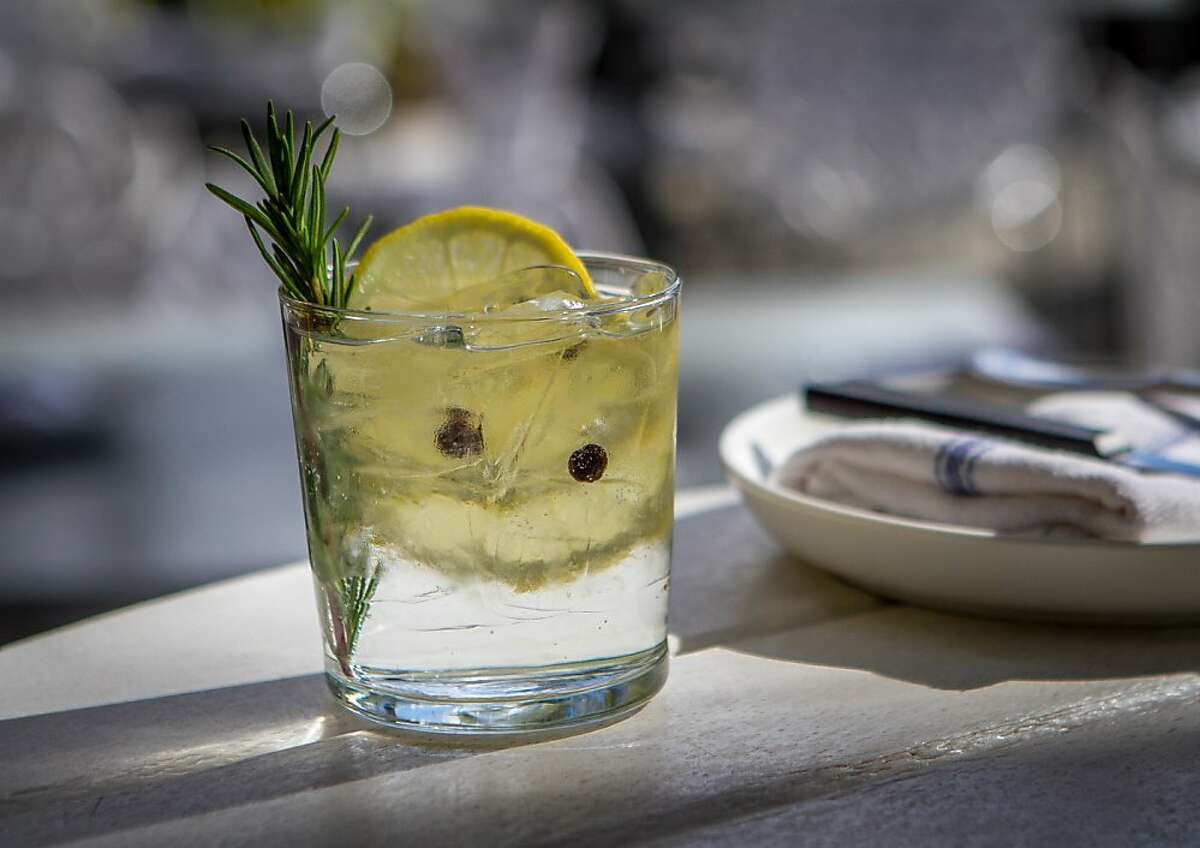 A sprig of rosemary doubles as a swizzle stick in the