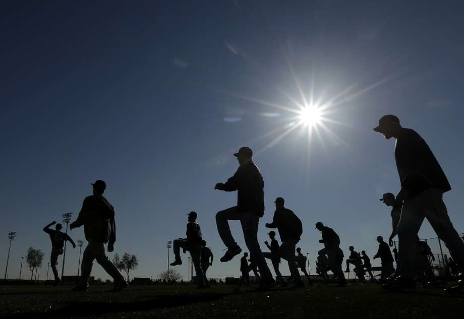 Ah, spring has hit Arizona, and so have the pitchers and catchers for the Seattle Mariners as they warm up Wednesday in Peoria, Ariz. (AP Photo/Charlie Riedel)