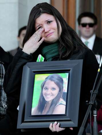 Heather Cronk, holds a photograph of her cousin of Sandy Hook Elementary School shooting victim teacher Victoria Soto,  as she wipes her eye during a rally at the Capitol in Hartford, Conn., Thursday, Feb. 14, 2013. Thousands of people turned out to call on lawmakers to toughen gun laws in light of the December elementary school shooting in Newtown that left 26 students and educators dead. Photo: Jessica Hill, AP Photo/Jessica Hill / Associated Press