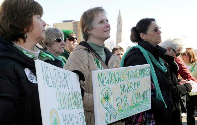 "Kathy Kloeblen, left, a school nurse at Newtown High School, and Sally Cox, a school nurse at Sandy Hook Elementary School, participate in Thursday  ""March for Change"" rally is held on the steps of the Capital in Hartford, Conn., Thursday, Feb. 14, 2013, to promote common sense and practical changes to the state's gun laws. Cox was working at the school the morning of the shooting. Photo: Carol Kaliff / The News-Times"