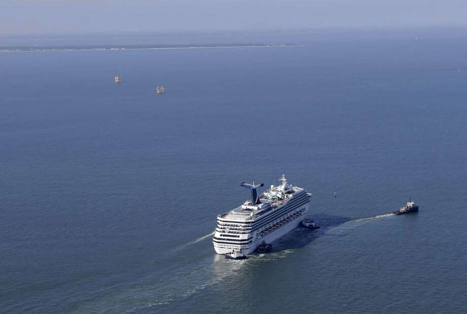 A disabled Carnival Lines cruise ship is towed to harbor off Mobile Bay, Ala., Thursday, Feb. 14, 2013.  The ship with over 1,000 passengers aboard has been idled for nearly a week in the Gulf of Mexico following an engine room fire. (AP Photo/Gerald Herbert) Photo: Gerald Herbert, Associated Press / AP