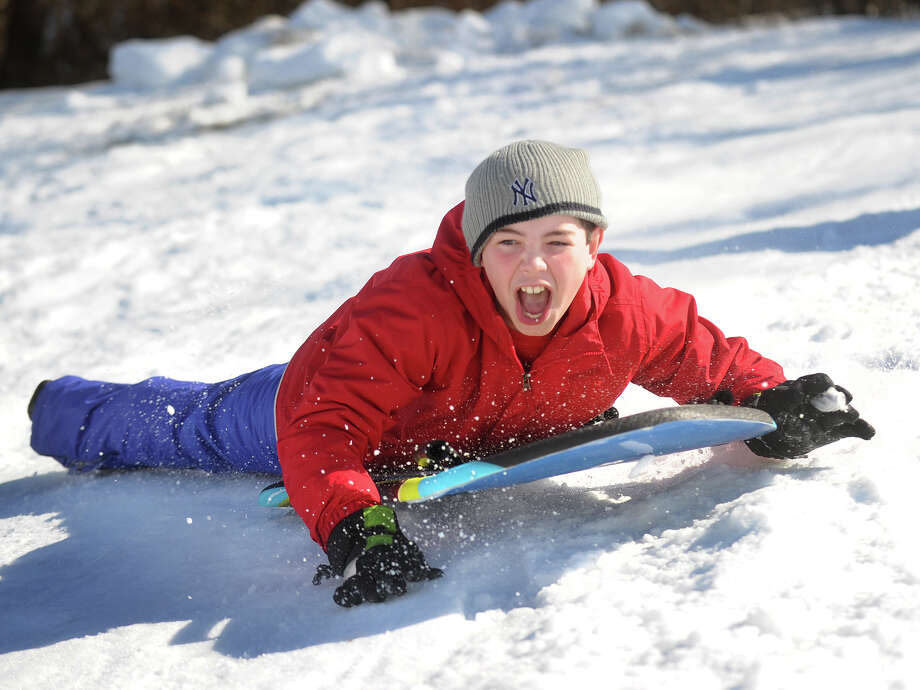 Alex Conte, 10 of Milford, gets turned sideways as he shoots down the sled hill at Foran High School in Milford on Thursday, February 14, 2013. Photo: Brian A. Pounds