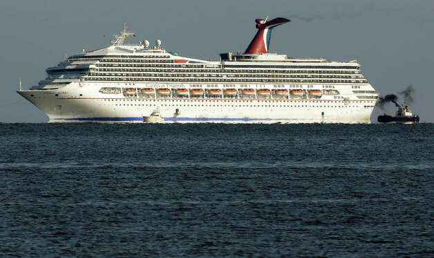 The cruise ship Carnival Triumph is towed towards Mobile Bay near Dauphin Island, Ala., Thursday, Feb. 14, 2013. The ship with over 1,000 passengers aboard has been idled for nearly a week in the Gulf of Mexico following an engine room fire. (AP Photo/Dave Martin) Photo: Dave Martin, Associated Press / AP