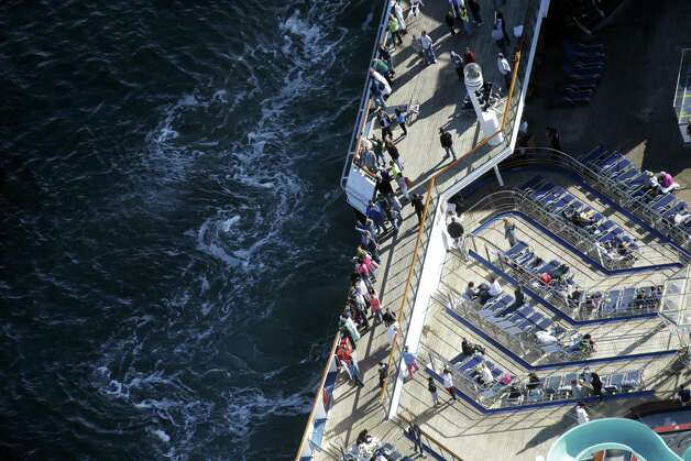 Passengers stand on the upper deck of the disabled Carnival Lines cruise ship Triumph as it is towed to harbor off Mobile Bay, Ala., Thursday, Feb. 14, 2013.  The ship with over 1,000 passengers aboard has been idled for nearly a week in the Gulf of Mexico following an engine room fire. (AP Photo/Gerald Herbert) Photo: Gerald Herbert, Associated Press / AP