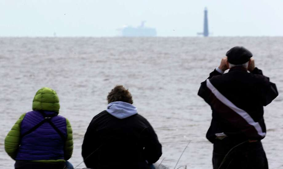 Residents sit on the shore and watch as the cruise ship Carnival Triumph is visible near Dauphin Island, Ala., Thursday, Feb. 14, 2013. The ship with over 1,000 passengers aboard has been idled for nearly a week in the Gulf of Mexico following an engine room fire. (AP Photo/Dave Martin) Photo: Dave Martin, Associated Press / AP