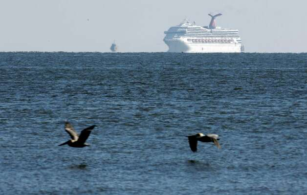 The cruise ship Carnival Triumph is visible several miles beyond the Sand Island Light House near Dauphin Island, Ala., Thursday, Feb. 14, 2013. The ship with over 4,000 passengers aboard has been idled for nearly a week in the Gulf of Mexico following an engine room fire, and is being towed to port in Mobile, Ala. (AP Photo/Dave Martin) Photo: Dave Martin, Associated Press / AP
